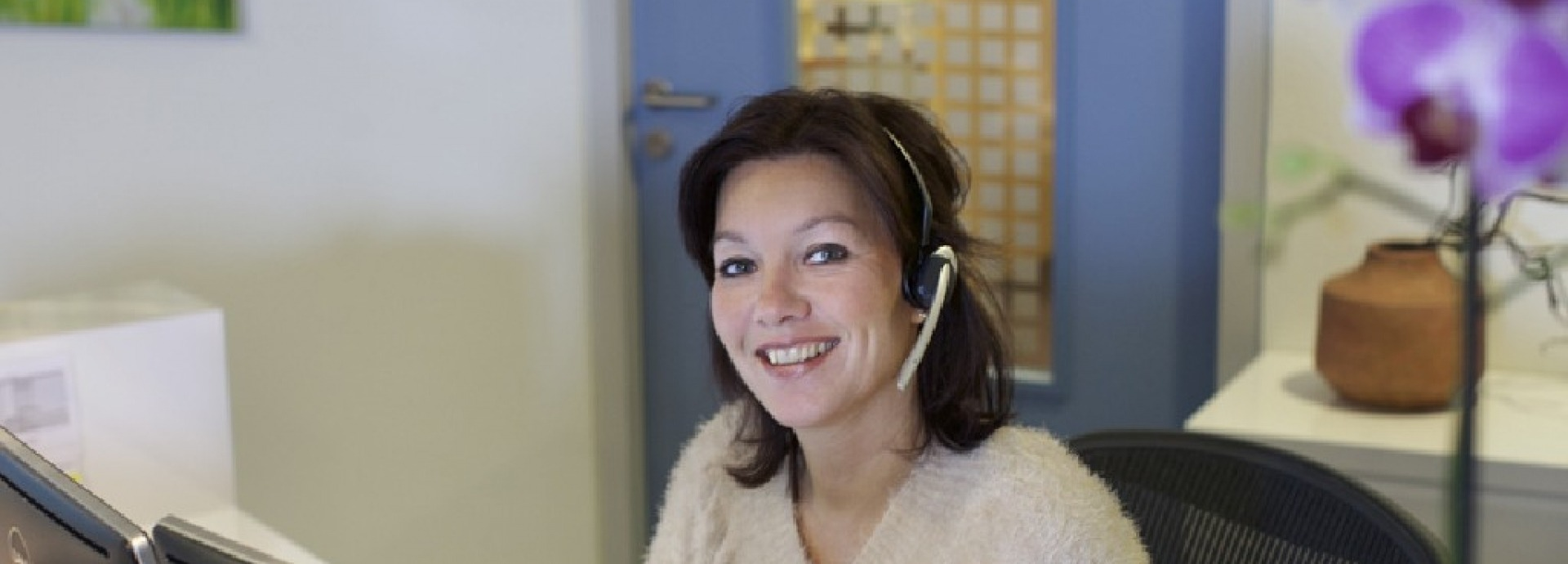 Een vrouw met koptelefoon achter haar computer bij de receptie